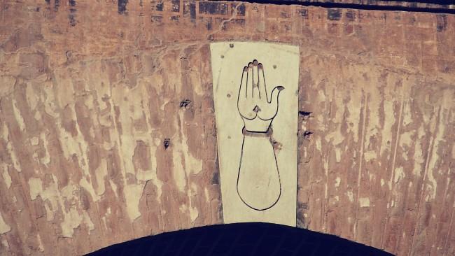 La mano con la palma extendida y abierta hacia nosotros sobre el arco de entrada